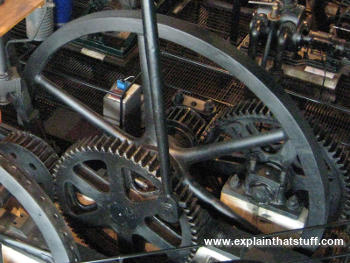 A large black flywheel with spokes attached to a gear wheel on a steam engine