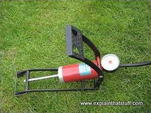 A red foot pump photographed on grass