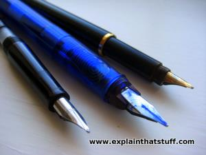 Three modern fountain pens arranged side by side.