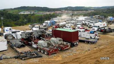 Trucks, pumps, well heads, and other equipment at a large fracking site.
