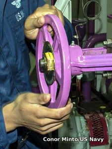 A stop valve being operated by hand.