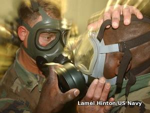Two military personnel check their gas mask air filters.