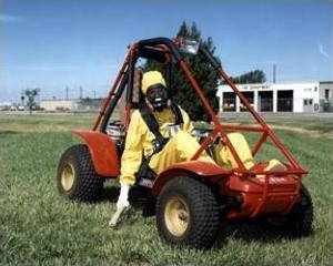 A man driving a buggy wearing a radiation suit and checking for radiation with a Geiger counter.