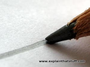 A red and black pencil laying a line of graphite on a white page.