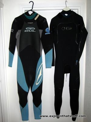 An old blind-stitched Gul wetsuit hanging next to a modern fluid-seam welded O'Neill wetsuit.