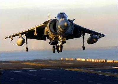 An AV-8B II Harrier lands on the flick deck of a ship.
