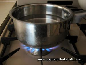 Heating water in an open saucepan on a gas stove.