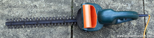 A green Black and Decker hedgecutter viewed from above.