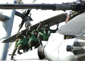 Four people holding the tail rotor of a US Navy helicopter
