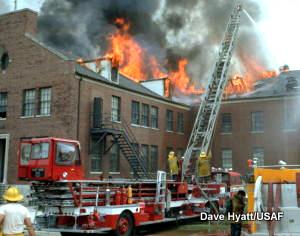 Firefighters tackle a burning building with hoses and extended turntable ladders.