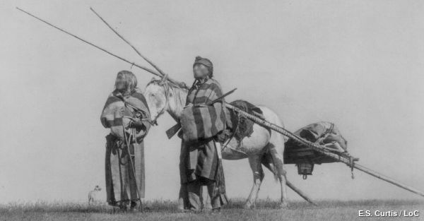 Two Native Americans walk alongside a horse and travois.