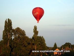 A red Virgin hot air balloon clears tall trees.
