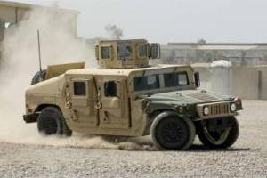 A US ARMY Humvee being driven quickly round a corner.