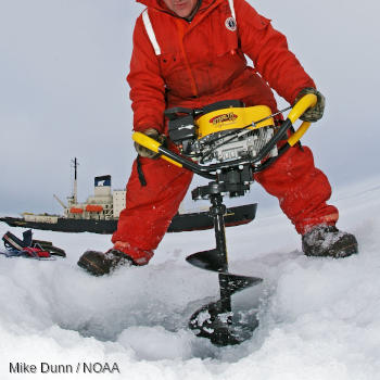 A man in a red suit drills an ice core by hand in Russia