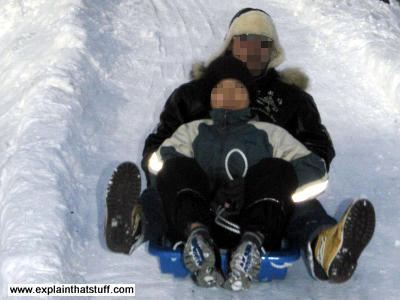 Two people slide down an icy hill on a sledge.