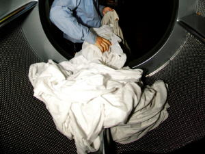 A man unloads sheets from a large launderette dryer, viewed from the inside looking out.