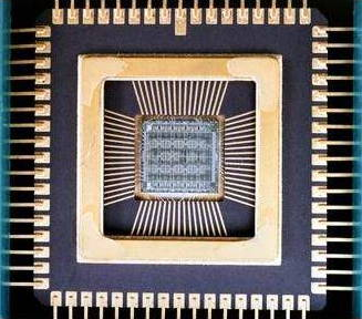 Inside a typical microchip. You can see the  integrated circuit and the wires that connect to the terminals around its edge.