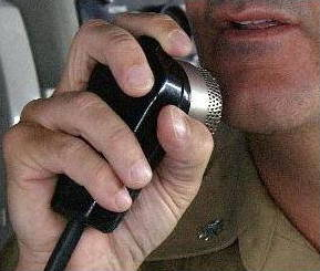 US Navy sailor talking into an intercom.