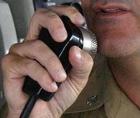 US Navy sailor talking into an intercom.