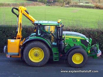 Side view of a John Deere tractor and hydraulic hedge cutter.
