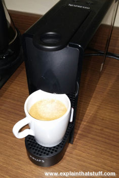 Slimline Krups Nespresso pod coffee maker with coffee cup in place.
