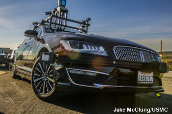 A black self-driving Lincoln MKZ car with onboard lidar and other scanners.