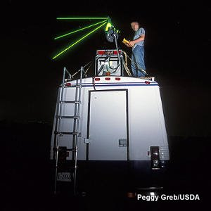 Green LIDAR laser beams fired from the roof of a scientific research truck.