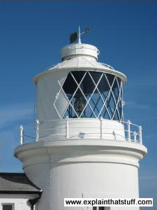 Closeup of a lighthouse tower showing the lamp and lens inside.