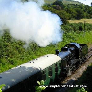 A black steam locomotive hauling carriages with a lot of white steam coming from its chimney.