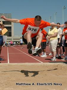 A long jumper flies through the air toward the sand in the pit.