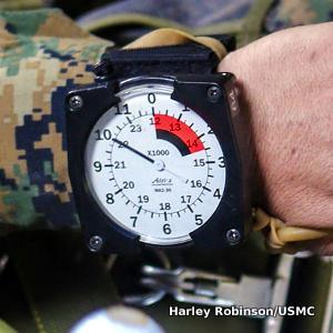 An Alti-2 MA2-30 parachute altimeter on a marine's wrist, reading 10,000ft on an analog display.