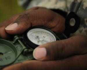 Hands holding a magnetic compass.
