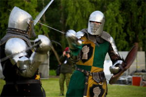 A pair of medieval knights dressed in armor fight with swords.