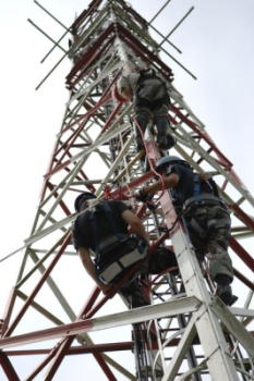 Telecommunications workers climb up the metal framework of an antenna