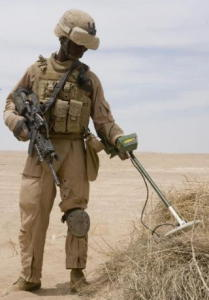 Soldier sweeping roadside for hidden weapons using a Garrett metal detector