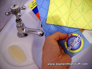 Two blue and yellow microfiber cleaning cloths being used in a washbasin.