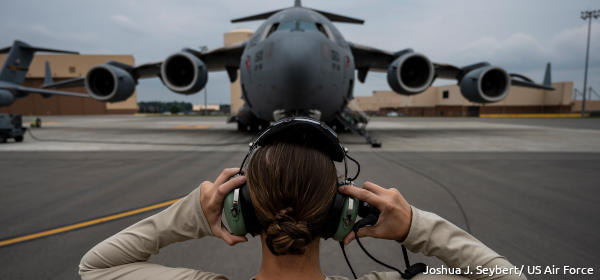 An airforce officer stands in front of a Globemaster plane and communicates with the pilot inside.