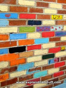 A wall in which each brick has been painted a different color by a graffiti artist.