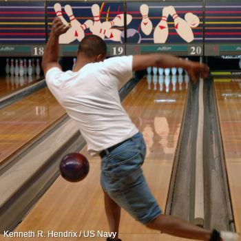 A man launches a red ball down a ten-pin bowling alley toward skittles.