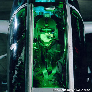 A helicopter pilot in the cockpit wearing cutting edge night vision goggles