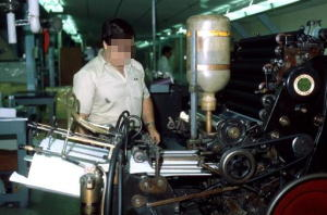 A man operates an old mechanical offset printing press.