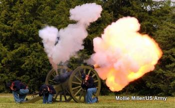 Photo of an old army cannon firing while three soldiers duck and cover their ears against the noise.