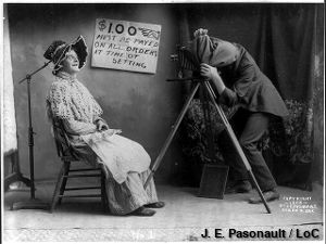 An old-fashioned photography session with a tripod camera and the photographer crouching under a cloth.