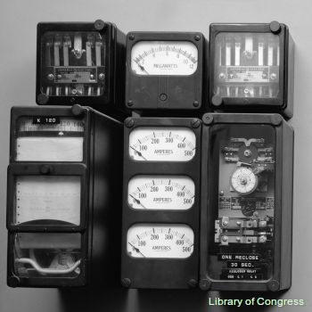Old-fashioned ammeters and power control equipment at an electricity power substation.