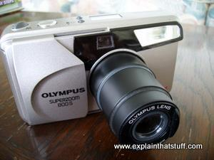 An Olympus 35mm film camera with telefoto zoom lens.