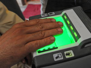 A man places his hand on a brightly lit optical scanner to have his fingerprints taken.
