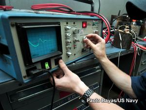 A US Navy electrician uses an oscilloscope to check the performance of an electric motor onboard an aircraft carrier.