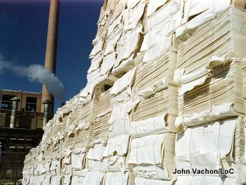 Paper stacked outside a paper mill with a smokestack in the background. Photo by John Vachon.