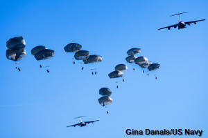 Many paratroopers dive to the ground together from two large planes.