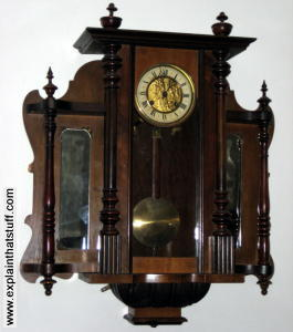 A wall-mounted wooden pendulum clock at Lanhydrock, Cornwall
